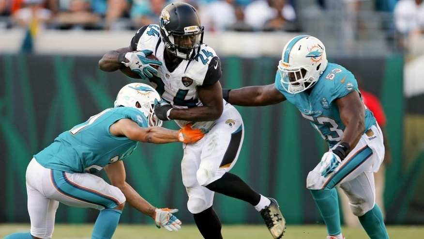 Jacksonville Jaguars running back T.J. Yeldon, center, runs between Miami Dolphins cornerback Brent Grimes, left, and outside linebacker Jelani Jenkins (53) during the second half of an NFL football game in Jacksonville, Fla., Sunday, Sept. 20, 2015. (AP Photo/Stephen B. Morton)