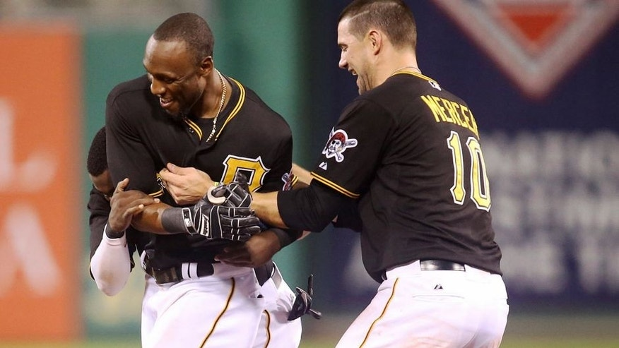 Jun 12, 2015; Pittsburgh, PA, USA; Pittsburgh Pirates third baseman Josh Harrison (hidden) and shortstop Jordy Mercer (10) celebrate with left fielder Starling Marte (middle) after Marte drove in the game winning run against the Philadelphia Phillies during the thirteenth inning at PNC Park. The Pirates won 1-0 in thirteen innings. Mandatory Credit: Charles LeClaire-USA TODAY Sports