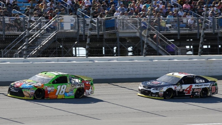 Kyle Busch (18) drives past Kevin Harvick (4) during the NASCAR Sprint Cup Series auto race at Chicagoland Speedway, Sunday, Sept. 20, 2015, in Joliet, Ill. (AP Photo/Nam Y. Huh)
