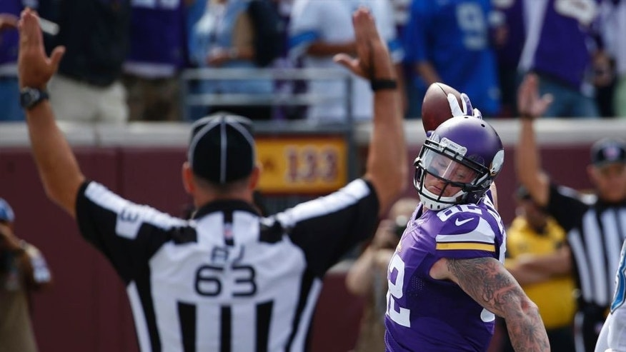 Minnesota Vikings tight end Kyle Rudolph celebrates his 5-yard touchdown catch against the Detroit Lions as back judge Jim Quirk signals in the first half in Minneapolis on Sunday, Sept. 20, 2015.