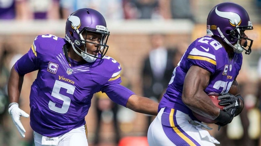 Minnesota Vikings quarterback Teddy Bridgewater hands the ball off to running back Adrian Peterson in the first half at TCF Bank Stadium in Minneapolis on Sunday, Sept. 20, 2015.