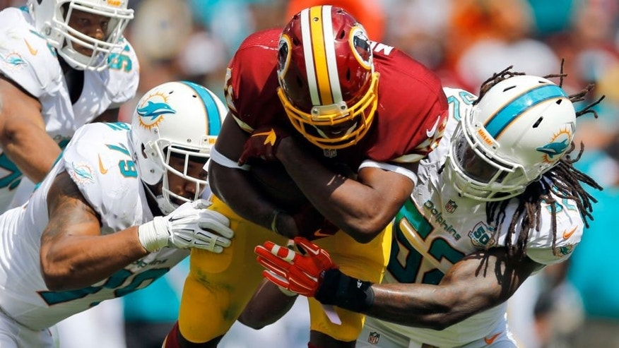 Miami Dolphins defensive end Derrick Shelby (79) and middle linebacker Kelvin Sheppard (52) tackle Washington Redskins running back Alfred Morris (46) during the first half of an NFL football game Sunday, Sept. 13, 2015, in Landover, Md. (AP Photo/Patrick Semansky)