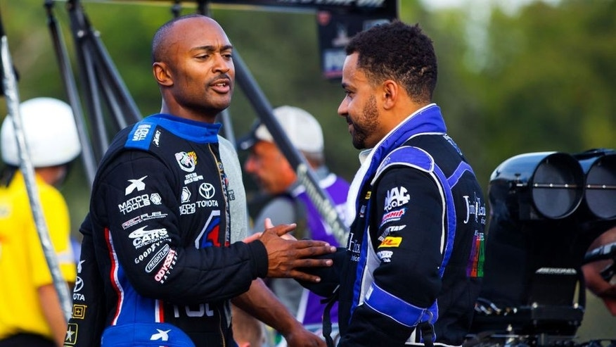 Sep 20, 2015; Concord, NC, USA; NHRA top fuel winner Antron Brown (left) greets runner up J.R. Todd following the final round of the Carolina Nationals at zMax Dragway. Mandatory Credit: Mark J. Rebilas-USA TODAY Sports