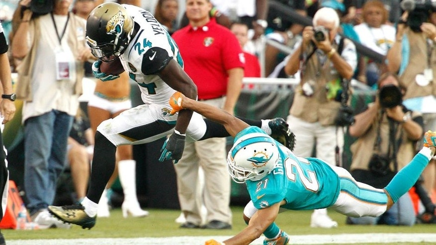 Sep 20, 2015; Jacksonville, FL, USA; Jacksonville Jaguars running back T.J. Yeldon (24) runs past Miami Dolphins cornerback Brent Grimes (21) during the second half of an NFL Football game at EverBank Field. The Jacksonville Jaguars won 23-20. Mandatory Credit: Reinhold Matay-USA TODAY Sports