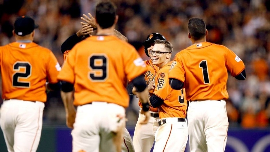 SAN FRANCISCO, CA - AUGUST 28: Kelby Tomlinson #37 of the San Francisco Giants is congratulated by teammates after he had the game-winning hit in the bottom of the ninth inning that scored Brandon Belt #9 against the St. Louis Cardinals at AT&T Park on August 28, 2015 in San Francisco, California. (Photo by Ezra Shaw/Getty Images)