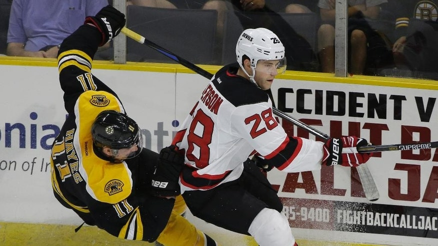 Boston Bruins right wing Jimmy Hayes, left, and New Jersey Devils defenseman Damon Severson, right, collide during the first period of an NHL preseason hockey game, Sunday, Sept. 20, 2015, in Providence, R.I. The Bruins won 2-0. (AP Photo/Steven Senne)