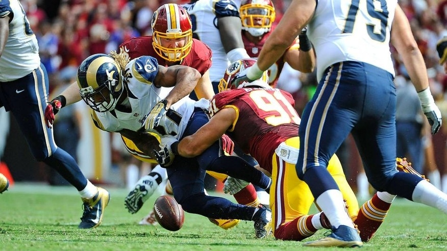 Sep 20, 2015; Landover, MD, USA; Washington Redskins outside linebacker Ryan Kerrigan (91) strips the ball from St. Louis Rams running back Tre Mason (27) during the second half at FedEx Field. The Washington Redskins won 24 - 10. Mandatory Credit: Brad Mills-USA TODAY Sports