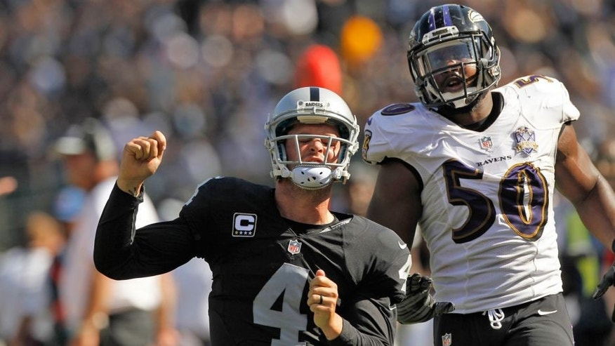 Sep 20, 2015; Oakland, CA, USA; Oakland Raiders quarterback Derek Carr (4) reacts in front of Baltimore Ravens outside linebacker Albert McClellan (50) after rushing for a first down in the third quarter at O.co Coliseum. The Raiders defeated the Ravens 37-33. Mandatory Credit: Cary Edmondson-USA TODAY Sports