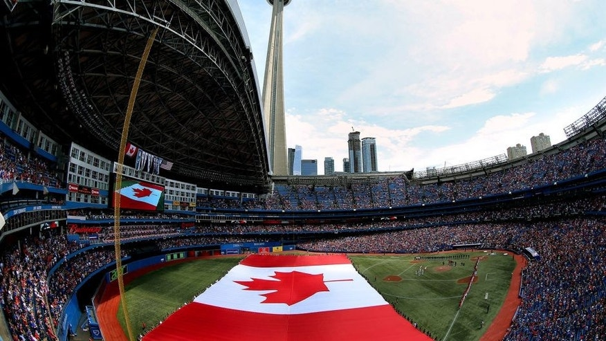 TORONTO, CANADA - JULY 1: A general view of the Rogers Centre on Canada Day as a large Canadian flag is unfurled on the field during the singing of the Canadian anthem before the start of the Toronto Blue Jays MLB game against the Milwaukee Brewers on July 1, 2014 at Rogers Centre in Toronto, Ontario, Canada. (Photo by Tom Szczerbowski/Getty Images)
