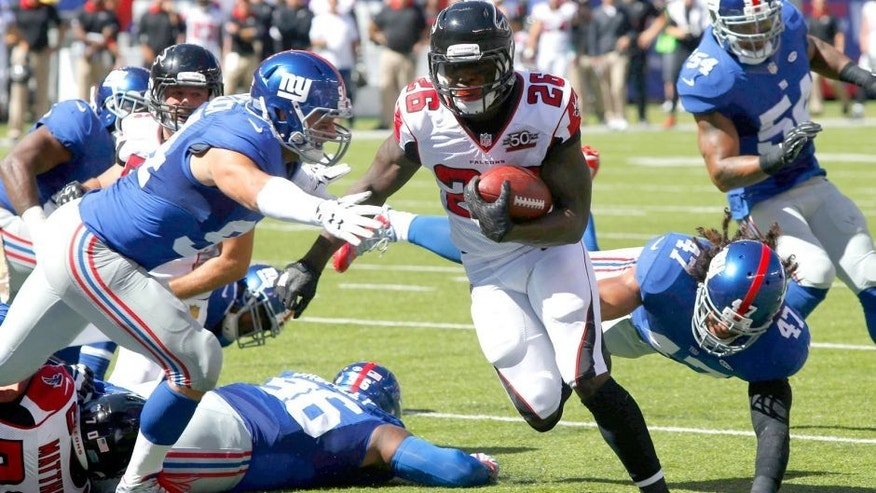 Sep 20, 2015; East Rutherford, NJ, USA; Atlanta Falcons running back Tevin Coleman (26) runs by New York Giants outside linebacker Mark Herzlich (94) and New York Giants middle linebacker Uani' Unga (47) for a touchdown during first half at MetLife Stadium. Mandatory Credit: Noah K. Murray-USA TODAY Sports