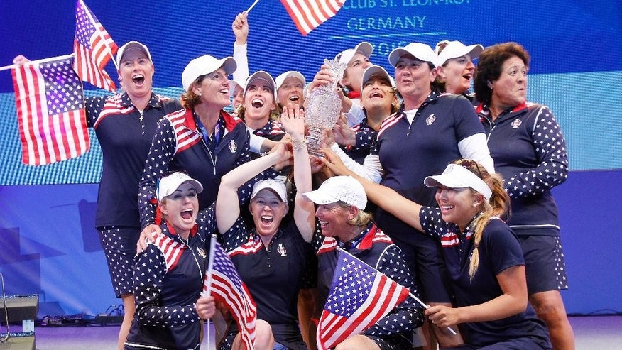 Team United States celebrates with the trophy after beating Europe in the Golf Solheim Cup in St.Leon-Rot, Germany, Sunday, Sept. 20, 2015.  Paula Creamer defeated Germany's Sandra Gal to complete a remarkable comeback as United States won the Solheim Cup with a 14½-13½ victory over Europe on Sunday. Creamer made five birdies in 15 holes to win the final singles match 4 and 3 and give the U.S. its first title since 2009.  ( AP Photo/Michael Probst)