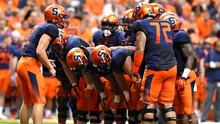 Sep 4, 2015; Syracuse, NY, USA; Syracuse Orange quarterback Eric Dungey (L) calls a play in the huddle against the Rhode Island Rams during the second quarter at the Carrier Dome. Syracuse won the game 47-0. Mandatory Credit: Rich Barnes-USA TODAY Sports