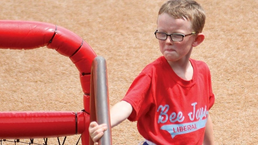 In this Aug. 1, 2015, photo, bat boy Kaiser Carlile, 9, gets ready for a National Baseball Congress World Series baseball game between the Liberal Bee Jays and San?Diego Waves outside the dugout in Wichita, Kan. Kaiser, who was wearing a helmet, was accidentally hit in the head during the game by a follow-through swing near the on-deck circle. He died on Sunday. (Earl Watt/Leader & Times via AP) MANDATORY CREDIT