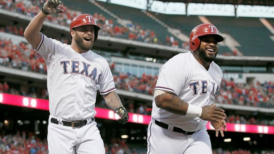 Texas Rangers' Mike Napoli, left, and Prince Fielder, right, celebrate a three-run home run by Napoli off Houston Astros' Dallas Keuchel during the first inning of a baseball game Wednesday, Sept. 16, 2015, in Arlington, Texas. The shot scored Fielder and Shin-Soo Choo. (AP Photo/Tony Gutierrez)