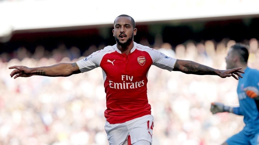 "Arsenal's English midfielder Theo Walcott celebrates scoring the opening goal during the English Premier League football match between Arsenal and Stoke City at the Emirates Stadium in London on September 12, 2015. AFP PHOTO / ADRIAN DENNIS RESTRICTED TO EDITORIAL USE. No use with unauthorised audio, video, data, fixture lists, club/league logos or ""live"" services. Online in-match use limited to 45 images, no video emulation. No use in betting, games or single club/league/player publications. (Photo credit should read ADRIAN DENNIS/AFP/Getty Images)"