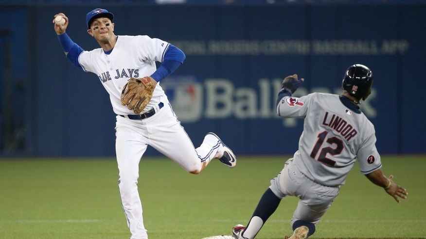 TORONTO, CANADA - SEPTEMBER 02: Troy Tulowitzki #2 of the Toronto Blue Jays turns a double play in the fourth inning during MLB game action as Francisco Lindor #12 of the Cleveland Indians slides into second base on September 2, 2015 at Rogers Centre in Toronto, Ontario, Canada. (Photo by Tom Szczerbowski/Getty Images)