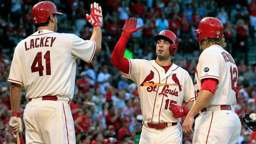 St. Louis Cardinals' Randal Grichuk, center, is congratulated by teammates John Lackey, left, and Mark Reynolds after hitting a two-run home run during the fifth inning of a baseball game against the New York Mets, Saturday, July 18, 2015, in St. Louis. (AP Photo/Jeff Roberson)