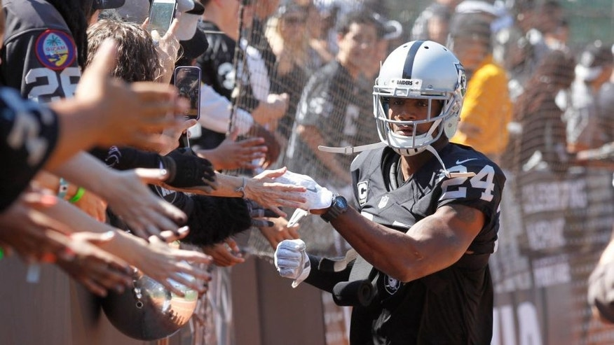 Sep 20, 2015; Oakland, CA, USA; Oakland Raiders free safety Charles Woodson (24) greets fans before the start of the game against the Baltimore Ravens at O.co Coliseum. Mandatory Credit: Cary Edmondson-USA TODAY Sports