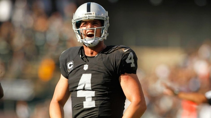Sep 20, 2015; Oakland, CA, USA; Oakland Raiders quarterback Derek Carr (4) reacts after throwing a touchdown pass against the Baltimore Ravens in the fourth quarter at O.co Coliseum. The Raiders defeated the Ravens 37-33. Mandatory Credit: Cary Edmondson-USA TODAY Sports