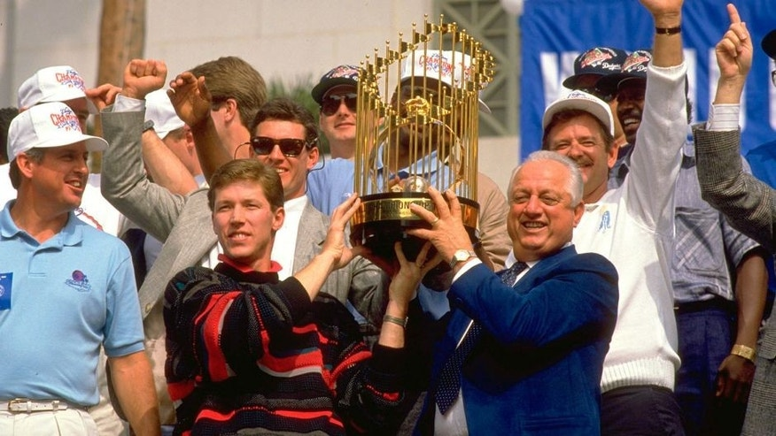 OCT 1988: TOMMY LASORDA, MANAGER OF THE LOS ANGELES DODGERS, AND OREL HERSHISER, PITCHER FOR THE DODGERS, HOIST THE MAJOR LEAGUE BASEBALL WORLD CHAMPIONSHIP TROPHY DURING THEIR 1988 CHAMPIONSHIP CELEBRATION AS OTHER MEMBERS OF THE TEAM WATCH FROM BEHIND.