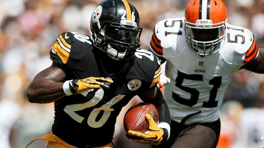 Sep 7, 2014; Pittsburgh, PA, USA; Pittsburgh Steelers running back Le'Veon Bell (26) runs the ball past Cleveland Browns linebacker Barkevious Mingo (51) during the first quarter at Heinz Field. Mandatory Credit: Jason Bridge-USA TODAY Sports