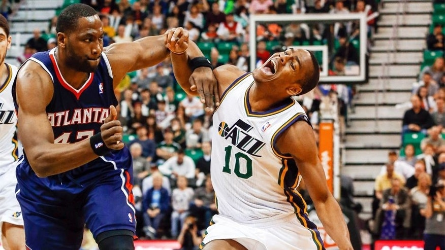 Mar 10, 2014; Salt Lake City, UT, USA; Utah Jazz point guard Alec Burks (10) is fouled by Atlanta Hawks power forward Elton Brand (42) during the third quarter at EnergySolutions Arena. The Atlanta Hawks won the game 112-110. Mandatory Credit: Chris Nicoll-USA TODAY Sports