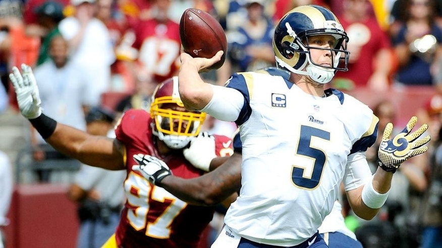 Sep 20, 2015; Landover, MD, USA; St. Louis Rams quarterback Nick Foles (5) attempts a pass as Washington Redskins defensive end Jason Hatcher (97) rushes during the first half at FedEx Field. Mandatory Credit: Brad Mills-USA TODAY Sports