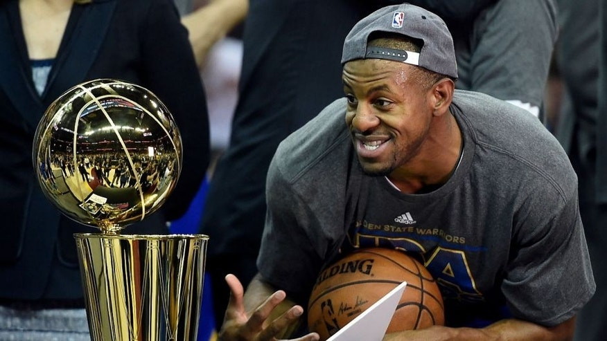 Jun 16, 2015; Cleveland, OH, USA; Golden State Warriors guard Andre Iguodala (9) reacts with the Larry O'Brien Trophy after beating the Cleveland Cavaliers in game six of the NBA Finals at Quicken Loans Arena. Mandatory Credit: Bob Donnan-USA TODAY Sports