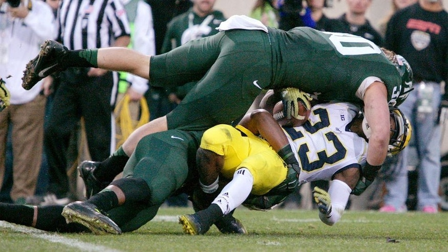 Michigan's Dennis Norfleet (23) is tackled on a kick return by Michigan State's Riley Bullough, top, and Montae Nicholson during the third quarter of an NCAA college football game, Saturday, Oct. 25, 2014, in East Lansing, Mich. Michigan State won 35-11. (AP Photo/Al Goldis)