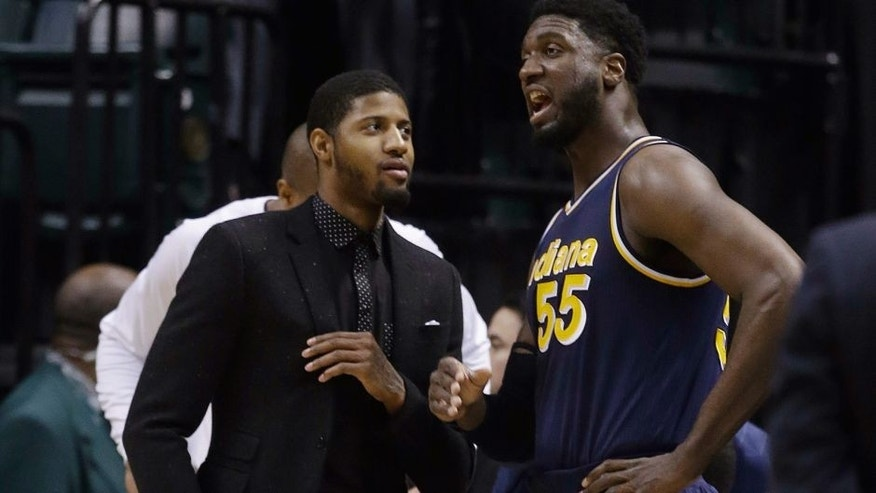 Indiana Pacers' Paul George, left, talks with Roy Hibbert (55) during the first half of an NBA basketball game against the Detroit Pistons, Wednesday, Feb. 4, 2015, in Indianapolis. (AP Photo/Darron Cummings)
