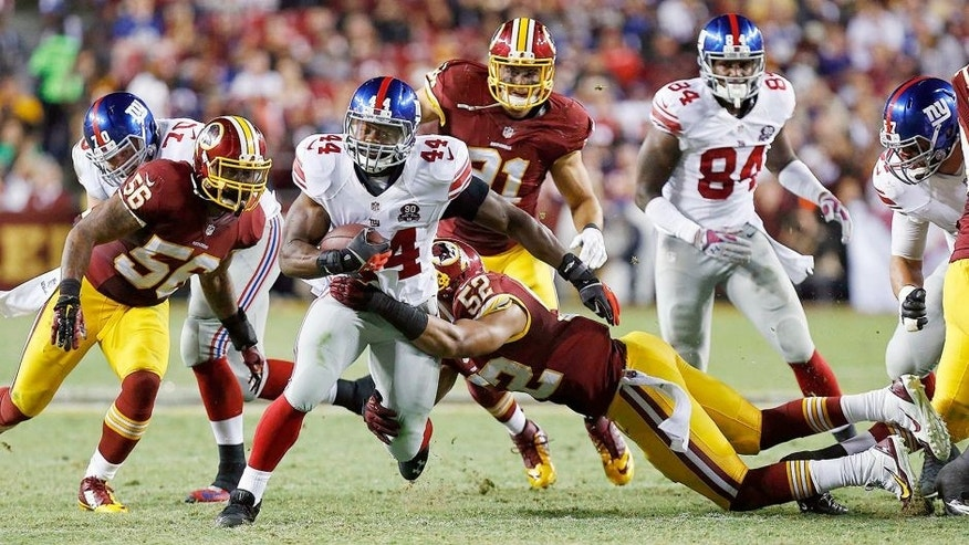 Sep 25, 2014; Landover, MD, USA; New York Giants running back Andre Williams (44) carries the ball as Washington Redskins inside linebacker Keenan Robinson (52) and Redskins inside linebacker Perry Riley (56) attempt the tackle in the third quarter at FedEx Field. The Giants won 45-14. Mandatory Credit: Geoff Burke-USA TODAY Sports