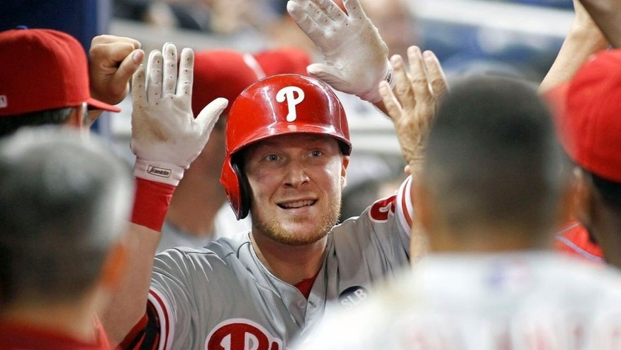 Philadelphia Phillies left fielder Cody Asche, center, is congratulated by teammates after his fourth inning home run against the Miami Marlins during a baseball game in Miami, Tuesday, Sept. 22, 2015. (AP Photo/Joe Skipper)