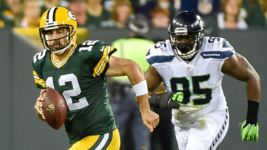 Sep 20, 2015; Green Bay, WI, USA; Green Bay Packers quarterback Aaron Rodgers (12) scrambles away from Seattle Seahawks defensive end Demarcus Dobbs (95) in the second quarter at Lambeau Field. Mandatory Credit: Benny Sieu-USA TODAY Sports