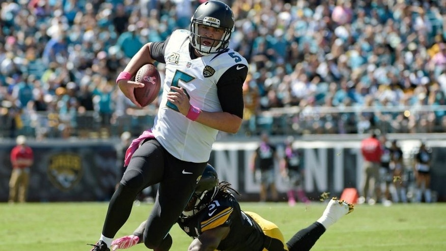 <p>Jacksonville Jaguars quarterback Blake Bortles (5) scrambles for yardage as he is pressured by Pittsburgh Steelers inside linebacker Sean Spence, bottom, during the first half of an NFL football game in Jacksonville, Fla., Sunday, Oct. 5, 2014. (AP Photo-Phelan M. Ebenhack)</p>