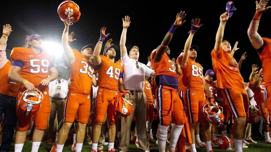 Dec 29, 2014; Orlando, FL, USA; Clemson Tigers players celebrate after the 2014 Russell Athletic Bowl at Florida Citrus Bowl. Clemson Tigers defeated the Oklahoma Sooners 40-6. Mandatory Credit: Joshua S. Kelly-USA TODAY Sports
