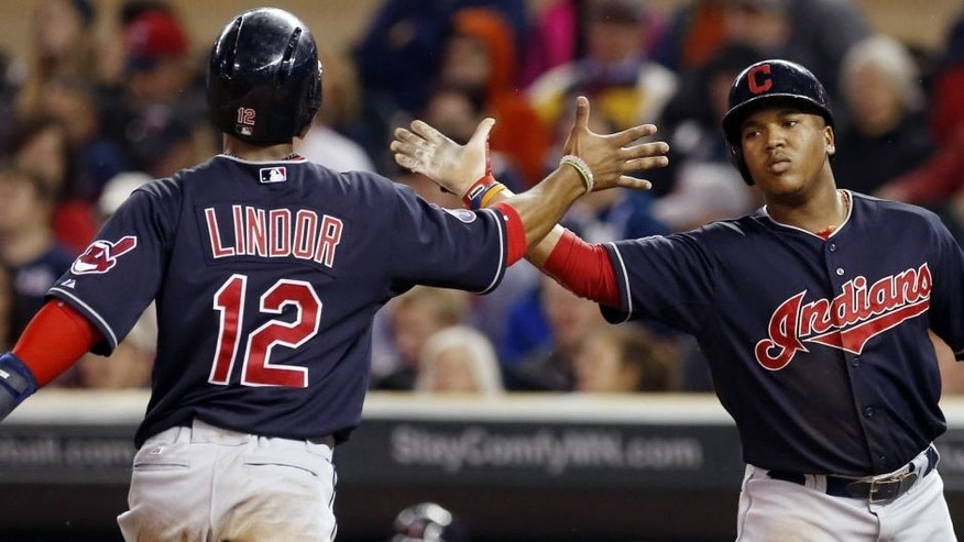 Cleveland Indians' Francisco Lindor, left, and Jose Ramirez celebrate after scoring on a two-run single by Lonnie Chisenhall off Minnesota Twins pitcher Kyle Gibson in the first inning of a baseball game, Thursday, Sept. 24, 2015, in Minneapolis.