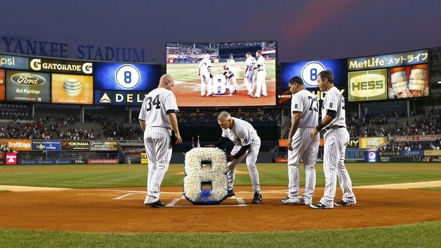 NEW YORK, NY - SEPTEMBER 24: Manager Joe Girardi #28 of the New York Yankees, with the help of Brian McCann #34, Gary Sanchez #73 and Austin Romine #53, place a floral bouquet in the shape of the number eight, over home plate in honor of Yogi Berra before a MLB baseball game against the Chicago White Sox at Yankee Stadium on September 24, 2015 in the Bronx borough of New York City. The Yankee legend passed away on Tuesday night at the age of 90. (Photo by Rich Schultz/Getty Images)