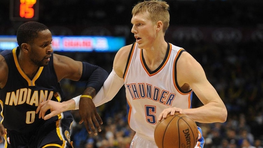 Feb 24, 2015; Oklahoma City, OK, USA; Oklahoma City Thunder forward Kyle Singler (5) handles the ball against Indiana Pacers guard C.J. Miles (0) during the first quarter at Chesapeake Energy Arena. Mandatory Credit: Mark D. Smith-USA TODAY Sports