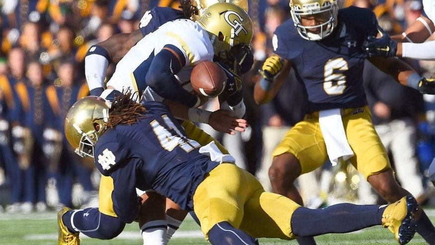 Sep 19, 2015; South Bend, IN, USA; Georgia Tech Yellow Jackets quarterback Justin Thomas (5) fumbles the ball against Notre Dame Fighting Irish cornerback Matthias Farley (41) during the second half at Notre Dame Stadium. Notre Dame defeats Georgia Tech 30-22. Mandatory Credit: Mike DiNovo-USA TODAY Sports