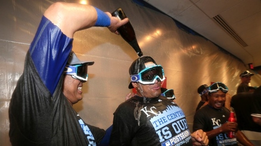 Kansas City Royals' Salvador Perez, left, pours champagne onto Francisco Pena in the clubhouse after the Royals clinched the AL Central with a 10-4 win over the Seattle Mariners in a baseball game Thursday, Sept. 24, 2015, in Kansas City, Mo. (AP Photo/Charlie Riedel)