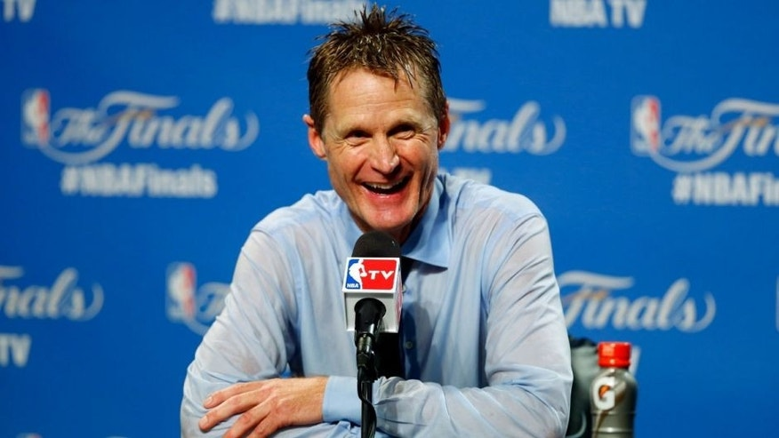 Golden State Warriors head coach Steve Kerr smiles during a news conference after the Warriors defeated the Cleveland Cavaliers, 105-97, in Game 6 of basketball's NBA Finals in Cleveland, Wednesday, June 17, 2015. The Warriors won the best-of-seven game series 4-2. (AP Photo/Paul Sancya)