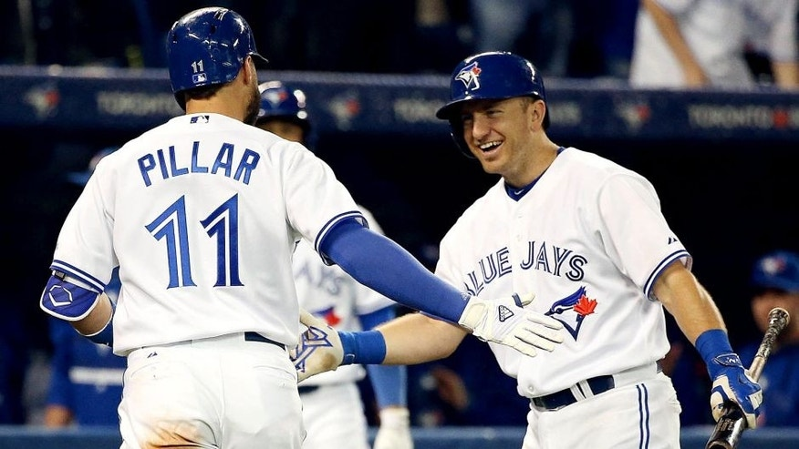 TORONTO, ON- SEPTEMBER 25 - Cliff Pennington congratulates Kevin Pillar after a home run in the fourth inning as the Toronto Blue Jays open a three game series against the Tampa Bay Rays at Rogers Centre in Toronto. September 25, 2015. (Steve Russell/Toronto Star via Getty Images)
