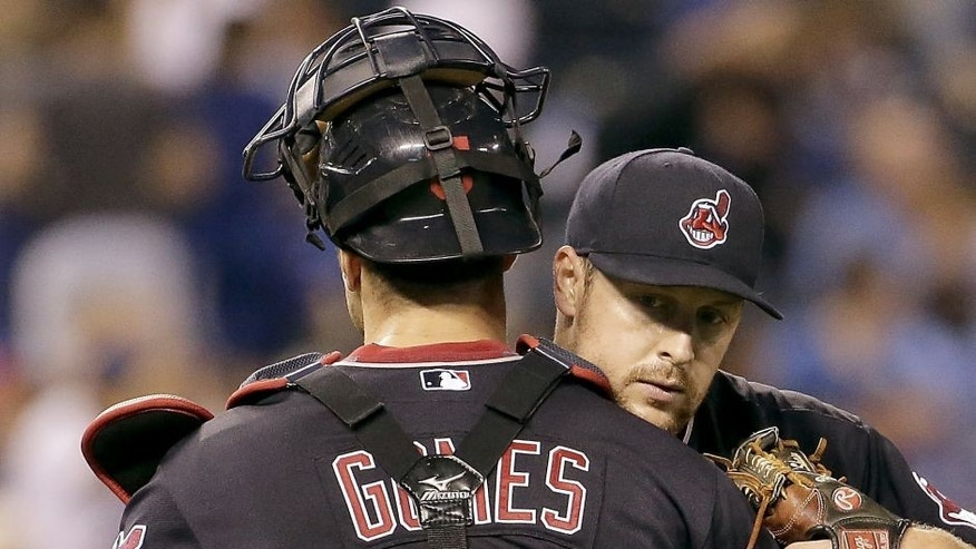 Cleveland Indians relief pitcher Bryan Shaw hugs catcher Yan Gomes after their baseball game against the Kansas City Royals Saturday, Sept. 26, 2015, in Kansas City, Mo. The Indians won 9-5.