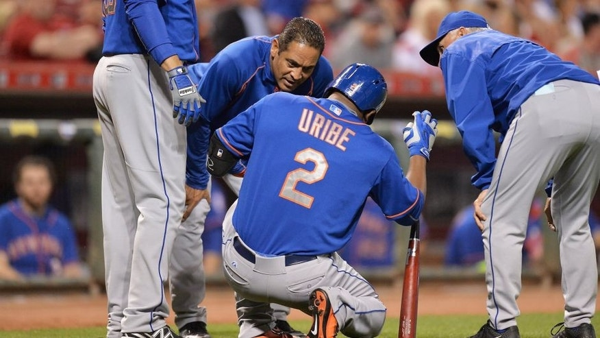 CINCINNATI, OH - SEPTEMBER 25: Juan Uribe #2 of the New York Mets is attended to by Mets personnel after injuring himself while batting against the Cincinnati Reds in the eighth inning at Great American Ball Park on September 25, 2015 in Cincinnati, Ohio. New York defeated Cincinnati 12-5. (Photo by Jamie Sabau/Getty Images)