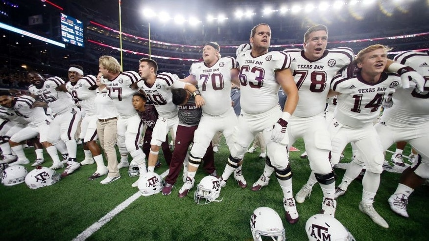 Texas A&M players gather with quarterback quarterback Kyle Allen (10) to sing their school song and celebrate a 28-21 overtime win in an NCAA college football game against Arkansas on Saturday, Sept. 26, 2015, in Arlington, Texas. (AP Photo/Tony Gutierrez)