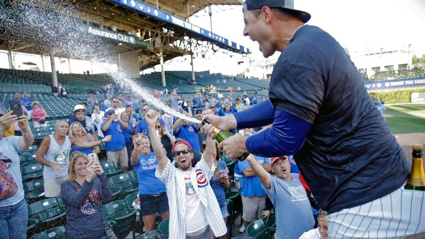 CHICAGO, IL - SEPTEMBER 26: Anthony Rizzo #44 of the Chicago Cubs celebrates with fans after clinching their wildcard playoff position at Wrigley Field on September 26, 2015 in Chicago, Illinois. (Photo by Jon Durr/Getty Images)