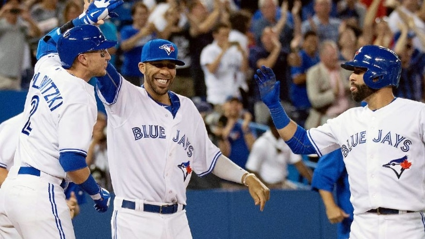 Jul 31, 2015; Toronto, Ontario, CAN; Toronto Blue Jays shortstop Troy Tulowitzki (2) and starting pitcher David Price (14) and right fielder Jose Bautista (19) celebrate the win during the eleventh inning in a game against the Kansas City Royals at Rogers Centre. The Toronto Blue Jays won 7-6. Mandatory Credit: Nick Turchiaro-USA TODAY Sports