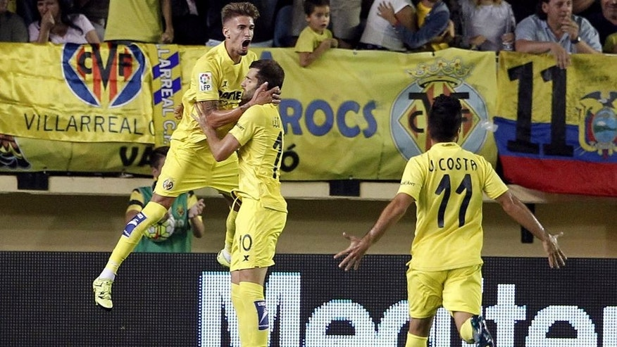 Villarreal's Brazilian forward Leonardo Carrilho Baptistao (L) celebrates his first goal during the Spanish league football match Villarreal CF vs Club Atletico de Madrid at El Madrigal stadium in Villareal on September 26, 2015. AFP PHOTO / JOSE JORDAN (Photo credit should read JOSE JORDAN/AFP/Getty Images)