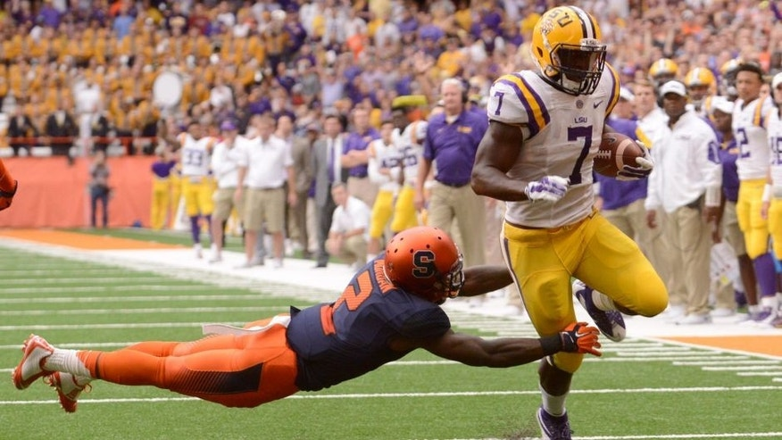 Sep 26, 2015; Syracuse, NY, USA; LSU Tigers running back Leonard Fournette (7) scores a touchdown after braking a tackle by Syracuse Orange cornerback Wayne Morgan (2) during the first quarter in a game at the Carrier Dome. Mandatory Credit: Mark Konezny-USA TODAY Sports