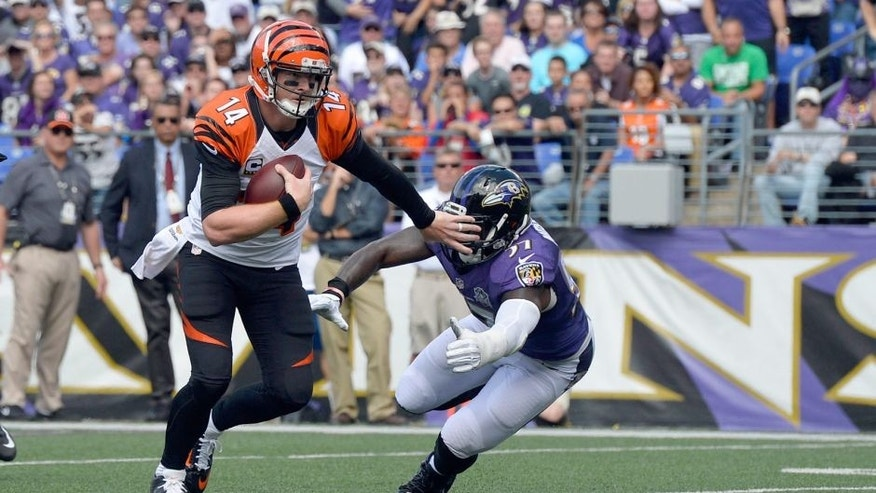 Sep 27, 2015; Baltimore, MD, USA; Cincinnati Bengals quarterback Andy Dalton (14) stiff arms Baltimore Ravens inside linebacker C.J. Mosley (57) as he run during the first quarter at M&T Bank Stadium. Mandatory Credit: Tommy Gilligan-USA TODAY Sports